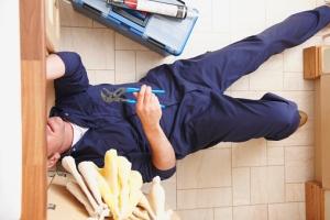 Overhead view of Caucasian plumber NYC repairing sink